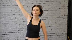 这录影是户内在健身房的年轻运动妇女舒展,手和身体肌肉 r 前面竞争 股票视频