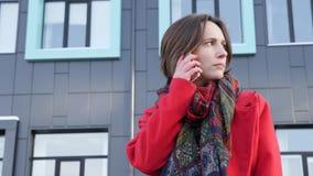 这录影是相当年轻女商人谈话由电话反对现代办公楼复合体在红色外套和围巾的 股票录像