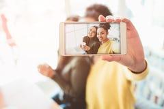 这是同时看很惊人和愉快两个美丽的女孩的selfie  在咖啡馆喝一些的他们 图库摄影