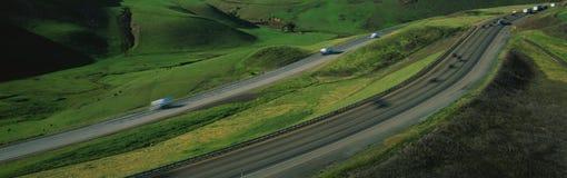 这是途径580在Altamont通过 有在高速公路的每边的绿草有两条不同路的汽车的对trave 免版税库存照片