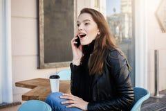 这样了不起的新闻 被打动的和激动的年轻欧洲女性画象坐在咖啡馆的时髦的成套装备的,喝 库存照片