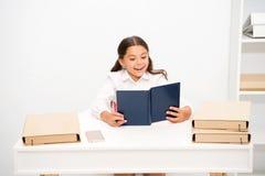 这样有趣的题目 当坐桌白色内部时,女孩孩子读了书 读书课本 女小学生学习 免版税库存图片