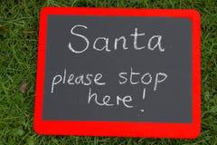 这里圣诞老人中止在与红色边界的blackoard签字 免版税库存图片