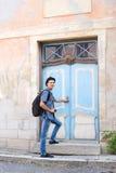 进入一个老大厦的英俊的男性游人 图库摄影