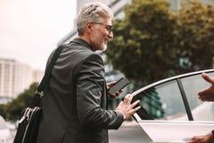 进入出租汽车的愉快的成熟通勤者 免版税库存图片