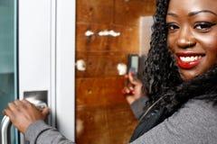 进入大厦的年轻非洲妇女 图库摄影