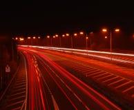 进入机动车路的汽车在晚上 免版税库存图片