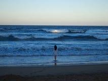 进入海洋的女孩在日落 免版税图库摄影