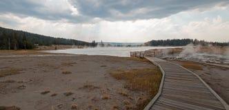 进入通过黑人战士温泉城和被缠结的小河的弯曲的高的木木板走道热的湖在黄石国家公园 库存照片