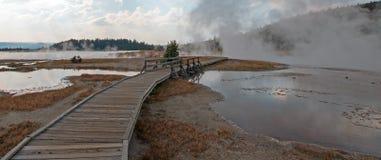 进入通过黑人战士温泉城和被缠结的小河的弯曲的高的木木板走道热的湖在黄石国家公园 免版税库存照片
