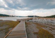 进入通过黑人战士温泉城和被缠结的小河的高的木木板走道热的湖在黄石国家公园 免版税库存照片