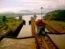进入巴拿马运河的游轮在琥珀色的日出下 免版税库存照片