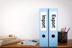 进口和出口黏合剂在办公室 在一个木架子的文具 免版税图库摄影