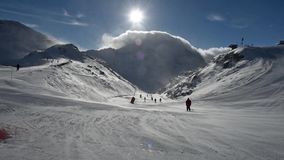 进来下坡在强风的滑雪道的滑雪者 影视素材