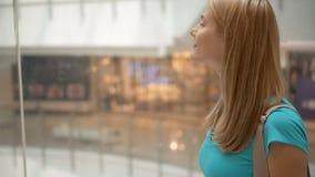 进来下来在购物中心电梯的绿松石T恤杉的愉快的微笑的少妇查寻 股票录像