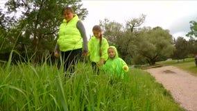 进来在绿色Gras的母亲和两个孩子 股票视频