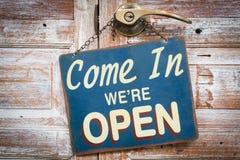 进来我们是开放的在木门,减速火箭的葡萄酒样式 库存照片