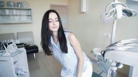 进来牙医办公室美女 患者在牙齿椅子,慢动作坐 影视素材