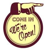 进来,我们是开放的!与指向手指的门商店可喜的迹象 免版税库存图片