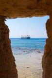 进行下去在一个石墙的一个开头的大蓝色船 风船航行看法在干尼亚州克利特通过在墙壁的一个窗口 Ho 图库摄影