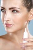 进行在她完善的面孔的美丽的妇女奶油色治疗 库存图片