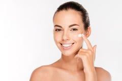 进行在她的面孔的美丽的少妇化妆奶油色治疗 库存照片