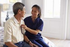进行在家访问的护士对身体检查的老人 库存图片