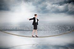 进行在绳索的女实业家的综合图象一次平衡操作 免版税库存照片