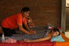 进行按摩的亚裔泰国妇女对欧洲少年男孩 免版税图库摄影