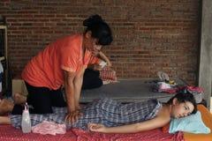 进行按摩的亚裔泰国妇女对欧洲少年男孩 免版税库存照片