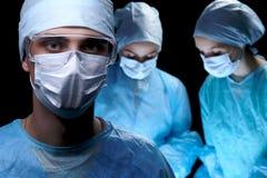 进行操作的医疗队 在男性医生的焦点 库存图片
