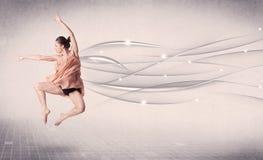 进行现代舞的跳芭蕾舞者与抽象线 库存照片