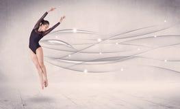 进行现代舞的跳芭蕾舞者与抽象线 图库摄影