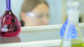 进行研究的女性研究员在化学实验室研究中心颜色一起定了调子图象浅DOF 免版税库存图片