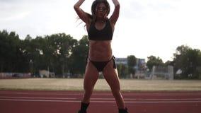 进行跳远的美丽的女运动员画象在解决在户外体育场的她期间 佩带 股票视频