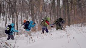 远征的四人 远足在困难的情况,人落入发生随风飘飞的雪 股票视频