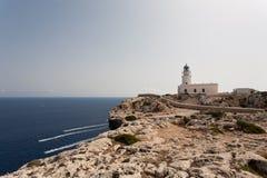 远的de Cavalleria -在峭壁的Cavalleria灯塔- Cap de Cavalleria梅诺卡岛Baleari海岛西班牙 库存图片