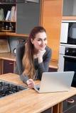 远程交换概念-愉快的少妇认为和与膝上型计算机一起使用 免版税库存图片