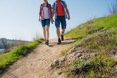 远足与在美丽的岩石足迹的背包的年轻夫妇晴朗的晚上 家庭旅行和冒险 免版税库存图片
