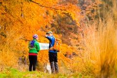 远足与地图的夫妇在秋天森林里 免版税库存照片