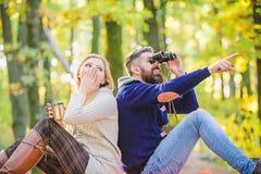远足与朋友 惊奇的女孩饮料加香料的热葡萄酒 r 有胡子的人有双筒望远镜的震惊手表 免版税库存图片