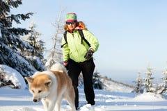 远足与狗的妇女冬天 免版税库存照片