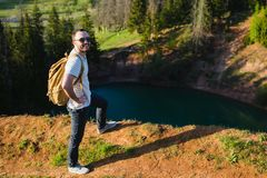 远足与走本质上的背包的人画象 白种人人微笑满意对森林在背景中在夏天期间 库存照片