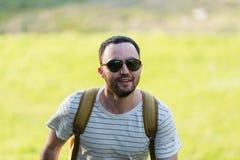 远足与走本质上的背包的人画象 白种人人微笑满意对森林在背景中在夏天期间 免版税库存图片