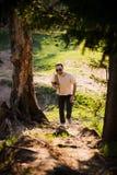 远足与走本质上的背包的人画象 白种人人微笑满意对森林在背景中在夏天期间 图库摄影