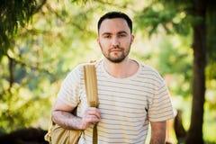 远足与走本质上的背包的人画象 白种人人微笑满意对森林在背景中在夏天期间 库存图片