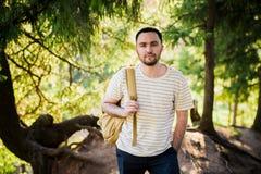 远足与走本质上的背包的人画象 白种人人微笑满意对森林在背景中在夏天期间 免版税图库摄影