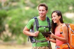 远足使用互联网app的片剂计算机的夫妇 免版税库存图片