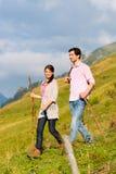 远足假期-男人和妇女阿尔卑斯山的 免版税库存图片