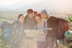 远足和看地图的人在他们的冒险期间 两个男人和两名妇女,探索山的徒步旅行者 库存图片